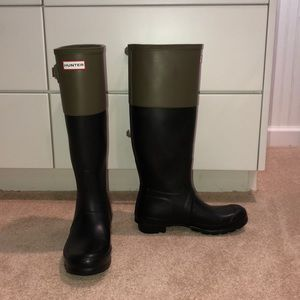 Tall black and green Hunter boots with socks